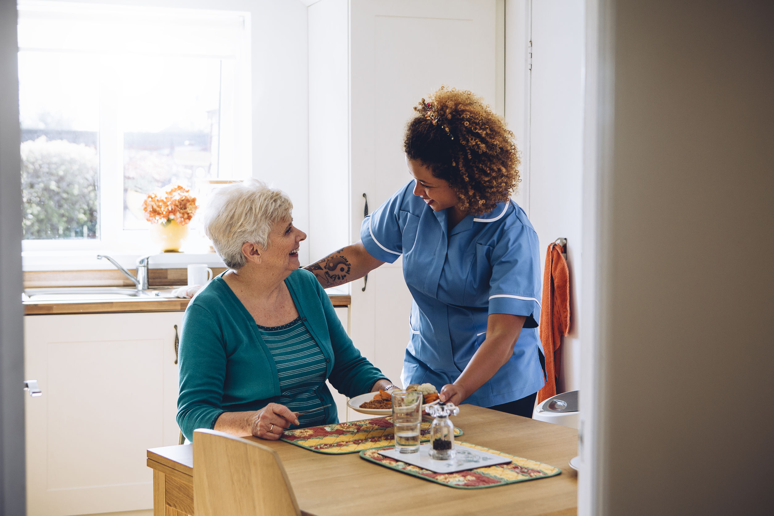 A care worker talks to an elderly woman in home care.