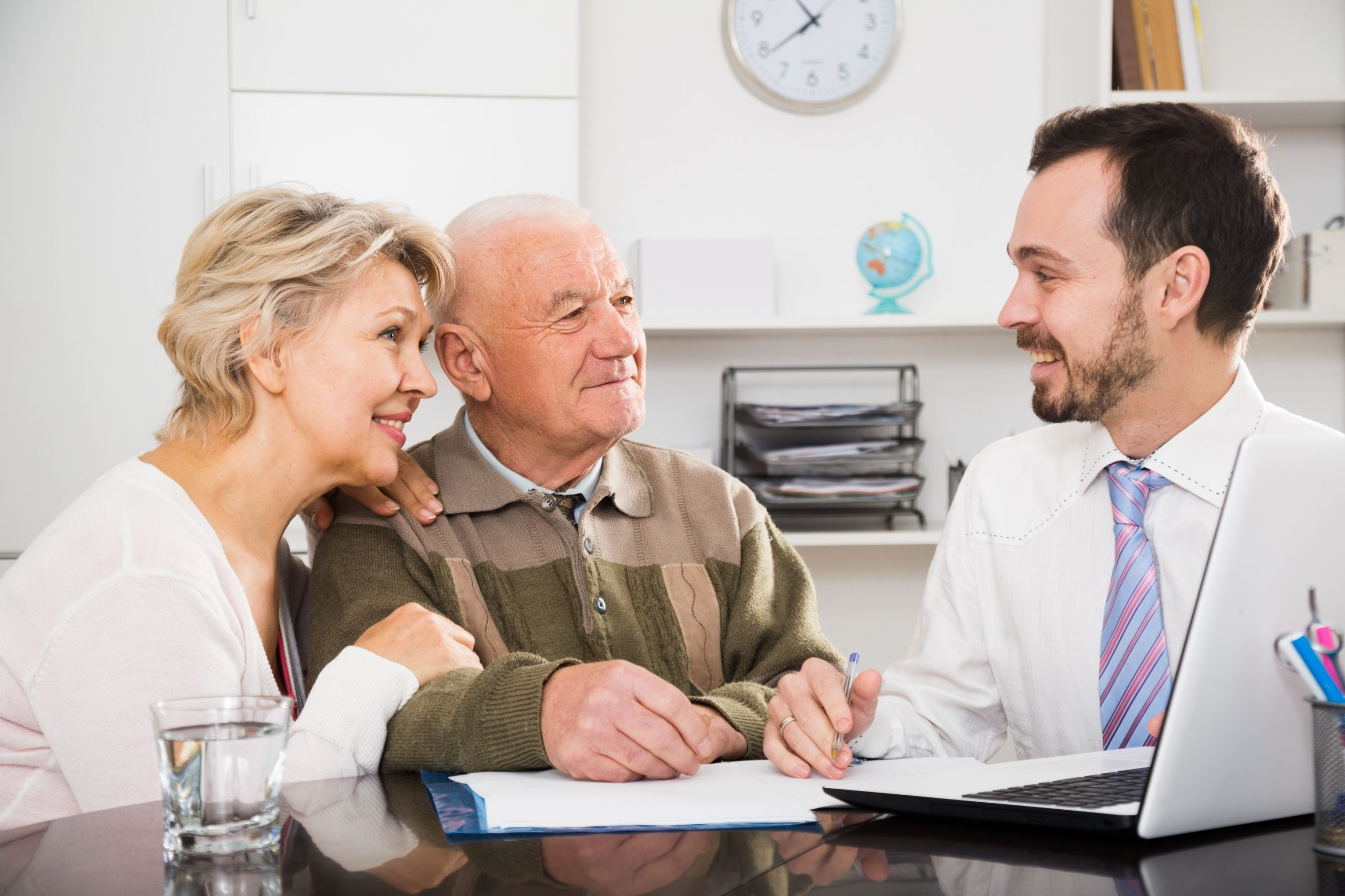 senior care franchise owner talking about paperwork with old couple