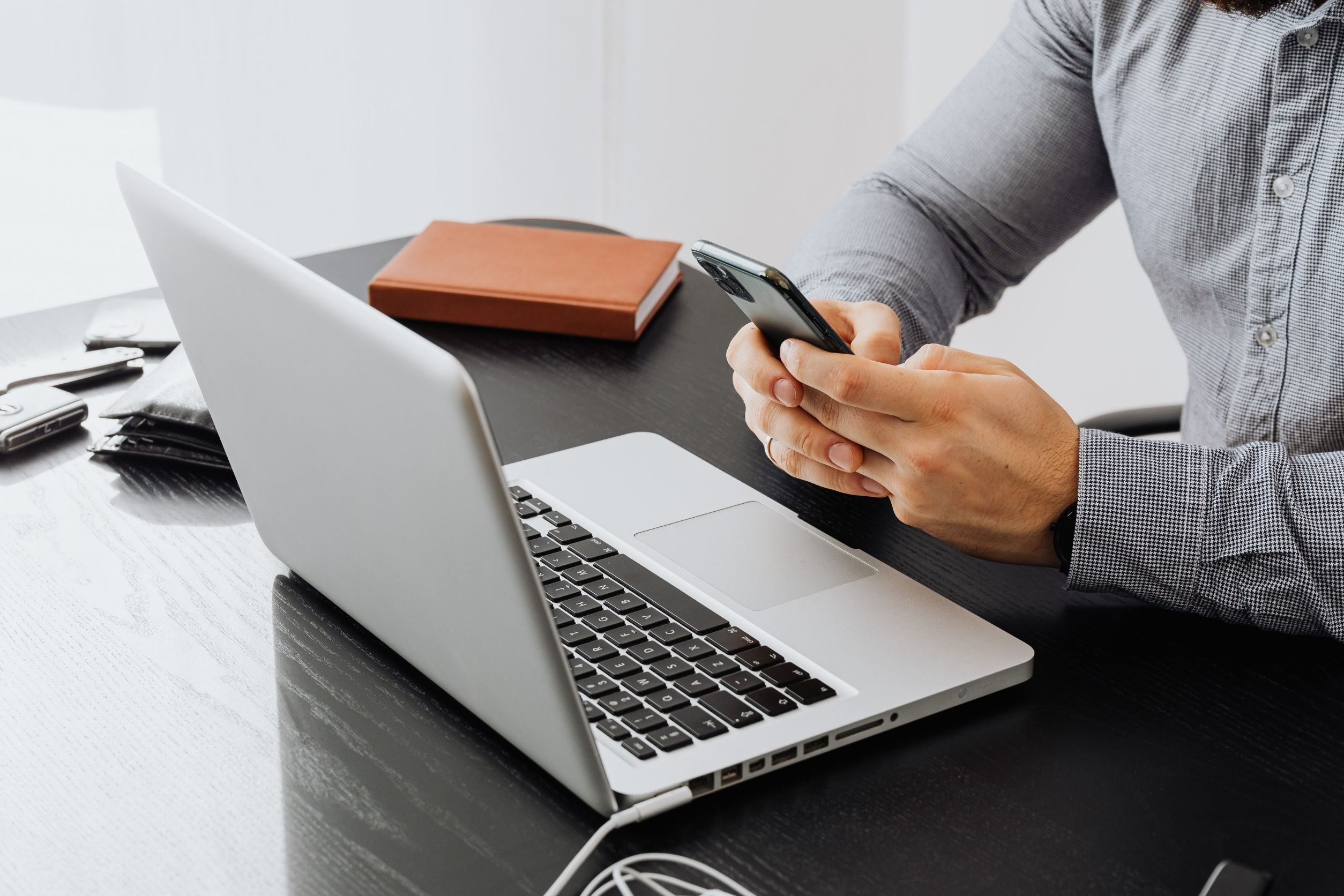 senior home care franchise owner wearing a gray shirt, using the phone and a laptop