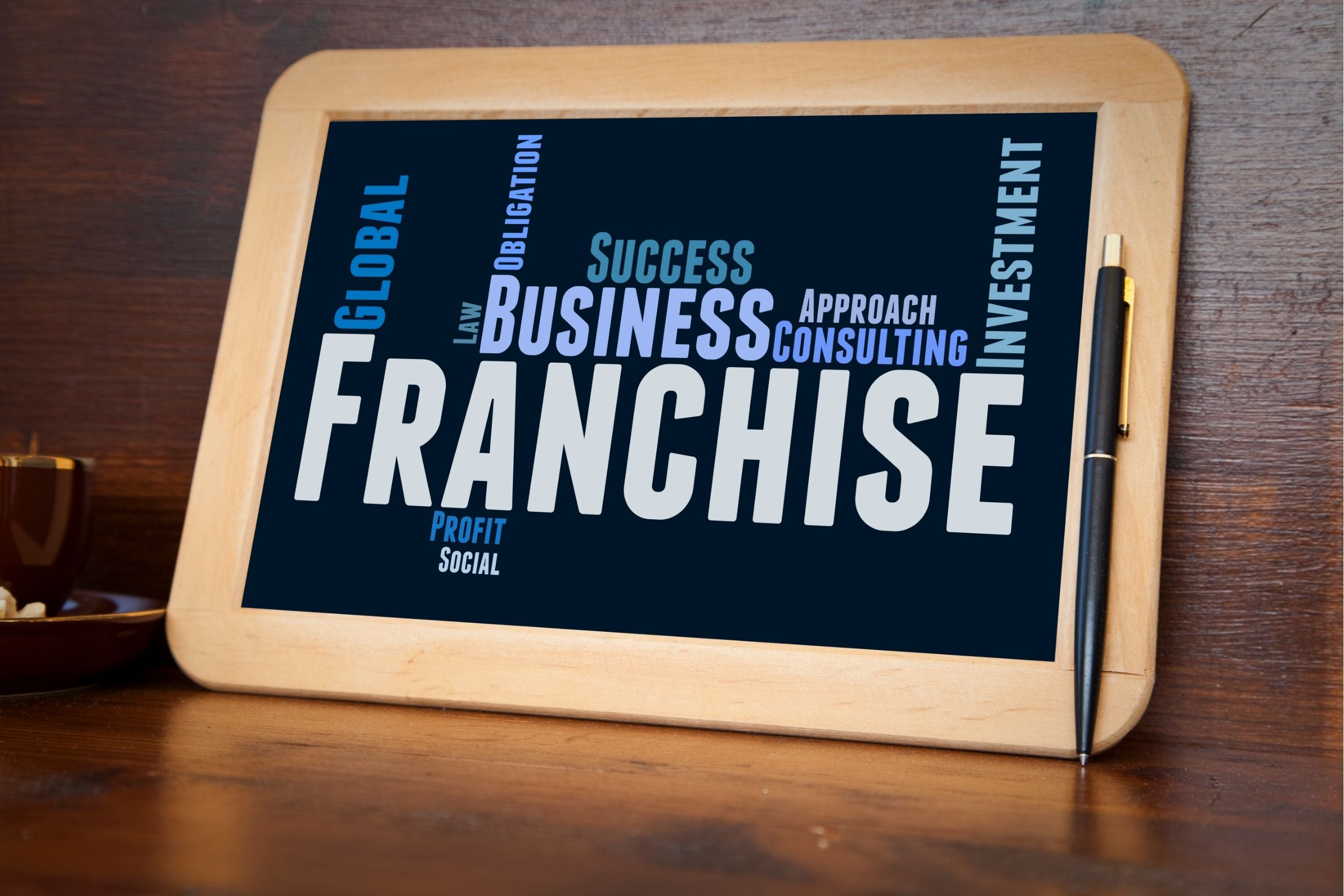Franchise business image concept displayed on tablet next to pen