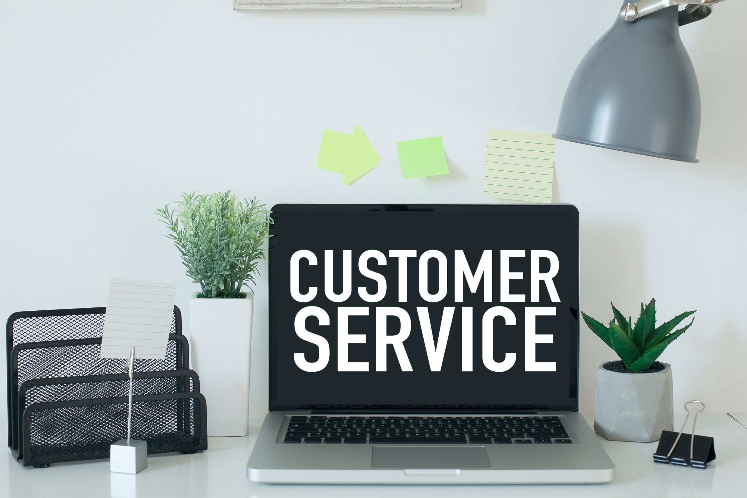 Customer services message displayed on laptop that is on desk next to plant and lamp