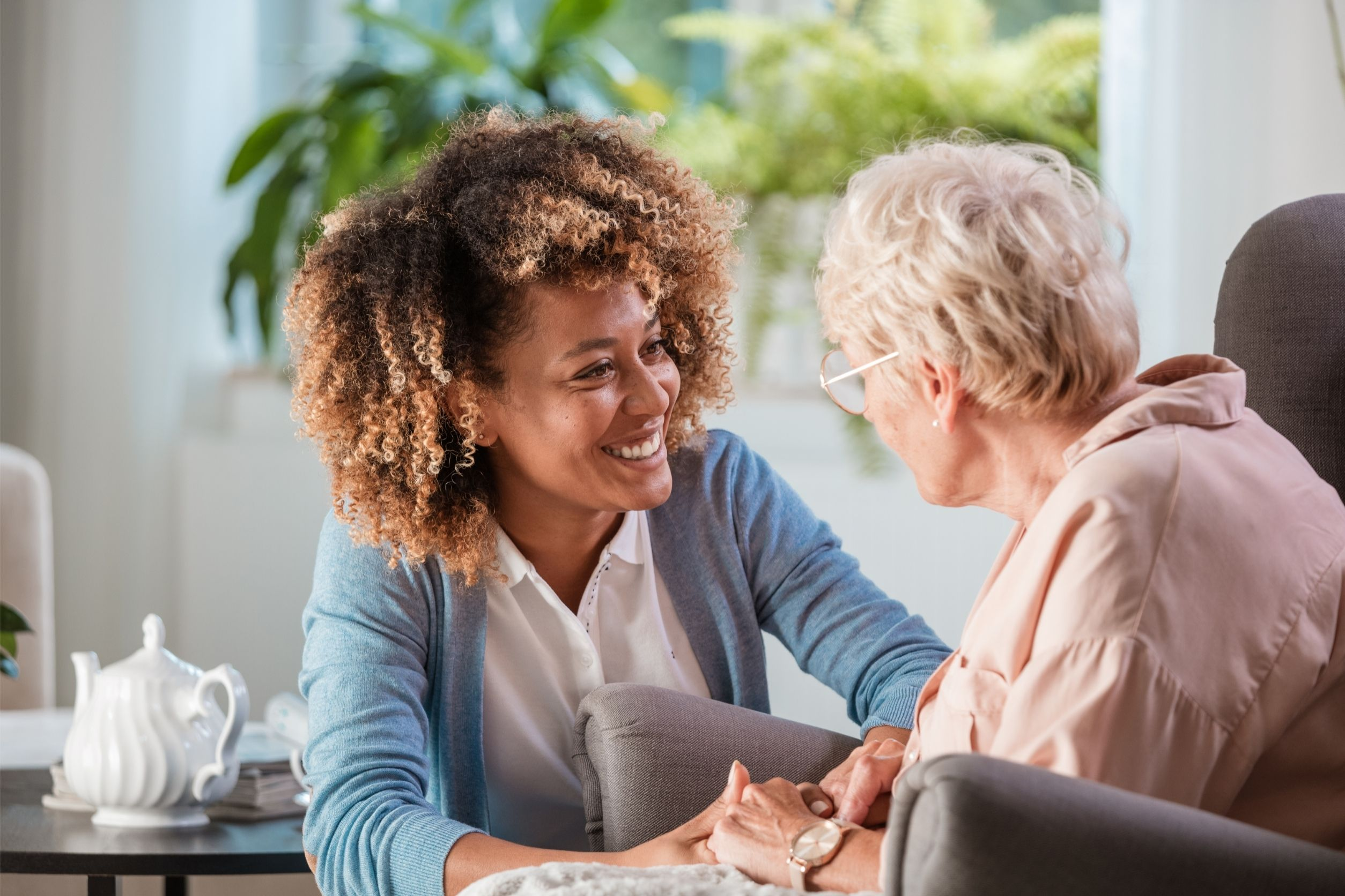 Happy caregiver taking care of senior woman at home